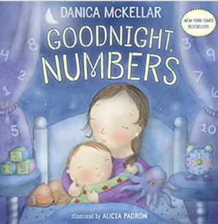"""The """"Goodnight Numbers' book cover is an image of mother and daughter hugging in a bed at night."""